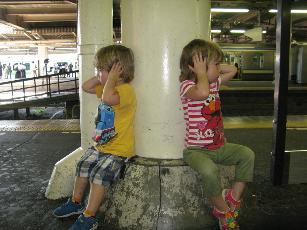 The kids cover the ears as a train pulls out of the station